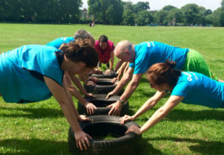 Quit the Gym Class members planking on tyres