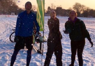 Three Quit the Gym members on a snowy field throwing snowballs towards the camera